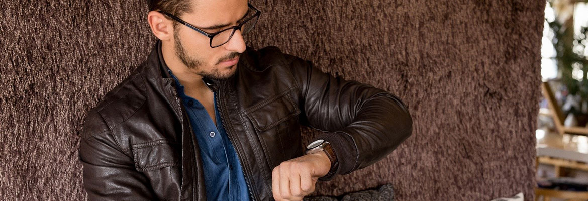 A man looking at a watch on his wrist